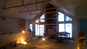 The Great Room. Kitchen is on the far left. Drywall hung, decorative beam framing in place.