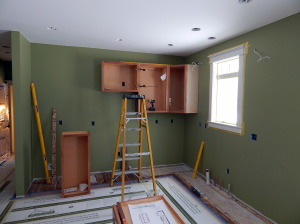 Paint is on the walls and cabinet installation has started.
