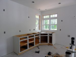 Setting Kitchen cabinets.