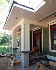 Installing stone to the front porch and road side elevation.
